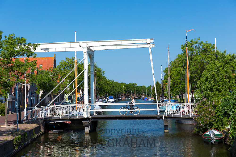 Woman cyclist cycling on bascule vertical-lift bridge, lift up drawbridge over canal waterway, Edam, The Netherlands