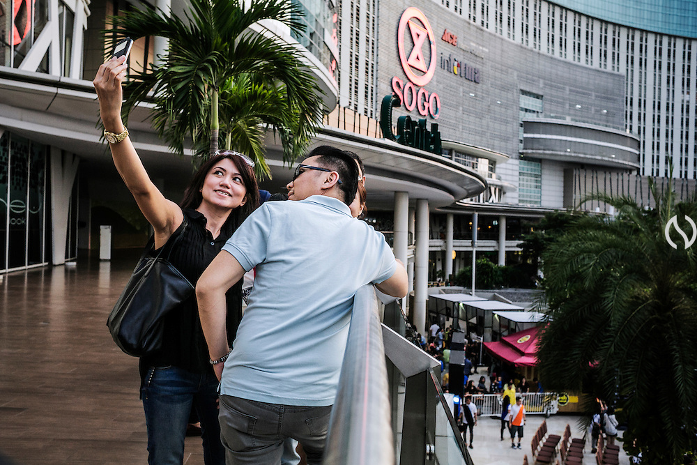 JAKARTA - INDONESIA; SATURDAY, SEPTEMBER 13, 2014; INDONESIA ECONOMIC RISING: Couples take selfie picture using camera phone while having week end vacation at Central Park Mall, Jakarta, Indonesia on Saturday, September 13, 2014. A complex with shopping mall, housing or apartment compound and recreational park have become a favourite for developers to build and residents as strategy of adaptation toward Jakarta frequently traffic jam. According to Asian Development Bank's 2014 report, Indonesia economy growth potential is in creative industry after for years relies heavily on natural resources such as mineral mining and palm oil. By the presidency of Joko Widodo, as a product of the third people election after the People Power Revolution in 1998, Indonesia is more confident in the economy growth and optimistic to become equal in quality to Brazil and China's economy growth. The emerging of Indonesia economy for the last one and a half decade after the end of Suharto's Dictatorship has been in significant way, the per capita growth has reached 400% under Susilo Bambang Yudhoyono presidency. Indonesia is home for 74 million of middle class as estimated by Boston Consulting Group, and  will double in 2020.