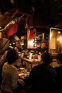 People in a small restaurant in Omoide-yokocho, an alley of small eateries serving yakatori in Shinjuku, Tokyo, Honshu, Japan