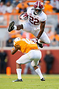 Alabama running back Najee Harris (22) hurdles Tennessee defensive back Nigel Warrior (18) as he runs the ball during the Crimson Tide's 58-21 victory over Tennessee in Neyland Stadium Saturday, Oct. 20, 2018. [Staff Photo/Gary Cosby Jr.]