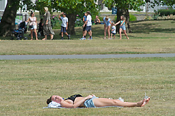 ©Licensed to London News Pictures 03/08/2020     Greenwich, UK. A lady sunbathing. People out and about in Greenwich Park, Greenwich, London making the most of the bright weather. Photo credit: Grant Falvey/LNP