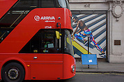 red bus and stylish and athletic model on a billboard for clothing retailer H&M, in central London.