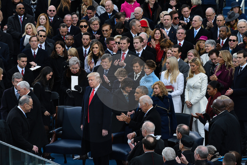 President Donald Trump stands as Vice President Mike Pence prepares to be sworn in during the 68th Inaugural ceremony January 20, 2017 in Washington, DC. Trump became the 45th President  of the United States of America.