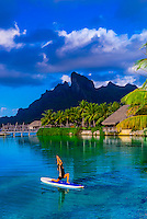 Woman doing standup paddleboard yoga in the lagoon, Four Seasons Resort Bora Bora, French Polynesia.