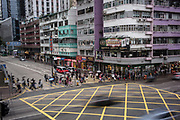Pedestrians cross a street lined with residential buildings and shophouses in Mong Kok, Kowloon, Hong Kong SAR on March 24th, 2019. Photo by Suzanne Lee/PANOS for Los Angeles Times