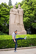 An elderly man exercises in front of a statue of Karl Marx and Friedrich Engel in Shanghai, China