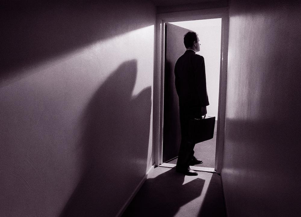 Businessman entering a light filled room.