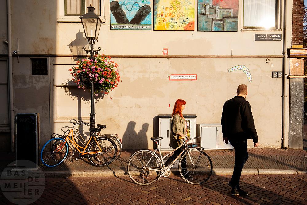 Een vrouw met een fiets in de hand loopt met een man door de Lange Smeestraat in Utrecht.<br /> <br /> A woman with a bicycle walks with a man in the city center of Utrecht.