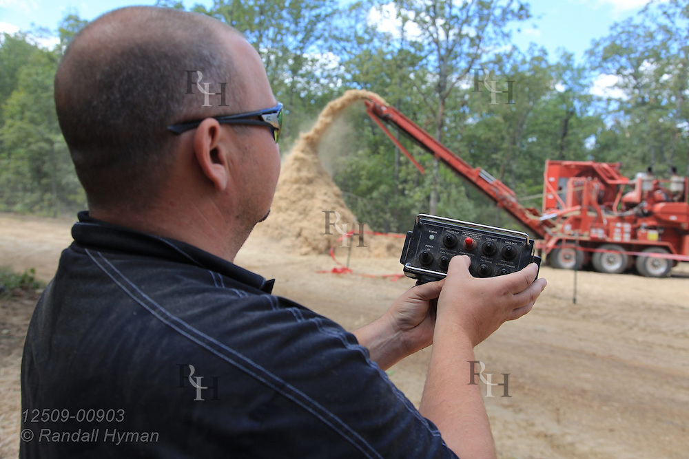 Man operates remote control equipment during ultra-mechanized clearcutting of an Ozarks woodland at Missouri In Woods Logging Demo near Viburnum, Missouri.
