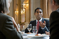 Three business people sitting at restaurant table talking