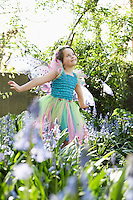 Young girl (5-6) in flower garden wearing fairy costume
