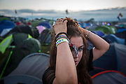 UNITED KINGDOM, Glastonbury: 22 June 2016 A revellers takes a break as she builds her tent at Glastonbury Festival this evening . Rick Findler / Story Picture Agency