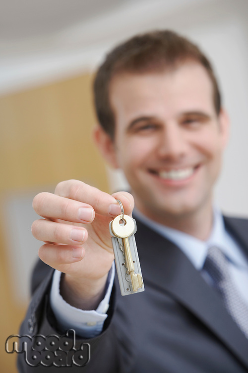 Real estate agent holding key indoors