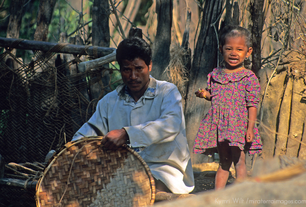 Asia, Nepal, Bardia. A young girl looks on as her father mends a rice basket.