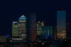© Licensed to London News Pictures. 24/03/2020. London, UK. The top of One Canada Square is seen illuminated in blue next to the empty offices of banks and financial institutions in London's Canary Wharf financial district this evening. This has been done in recognition and appreciation of National Health Service (NHS) staff working in hospitals across the country during the ongoing COVID-19 coronavirus epidemic. Photo credit: Vickie Flores/LNP