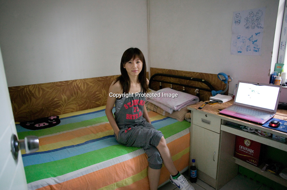 BEIJING, JULY-22, 2010  : A YOUNG WOMAN SITS N A BED IN HER TINY ROOM IN THE BASEMENT OF A HIGH RISE.