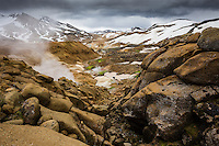 Kerlingarfjöll geothermal area, Highlands of Iceland. Brown lava boulders in forground and steam from geothermal vents and mudpools in background. Mount Fannborg and Snækollur above.