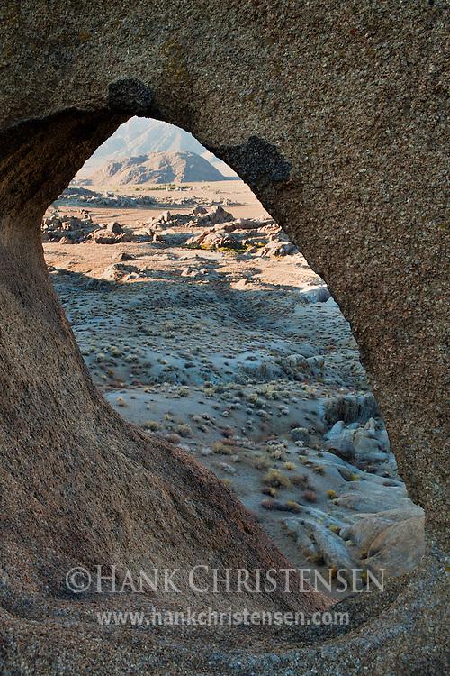 A natural arch frames a high desert landscape, Alabama Hills, CA