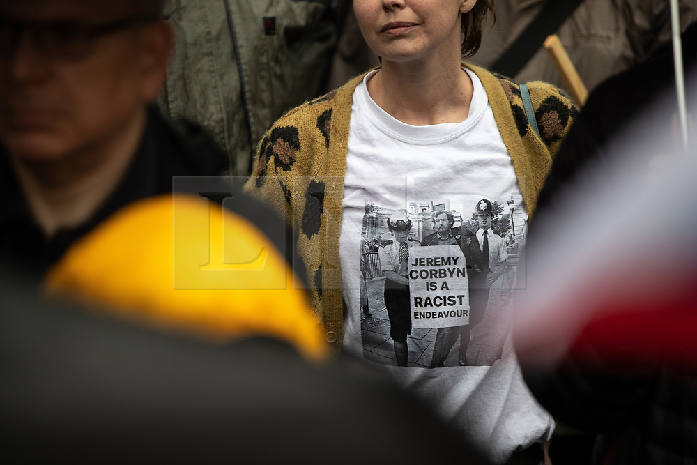 "© Licensed to London News Pictures . 16/09/2018. Manchester, UK. A woman wearing a t-shirt with a photograph of Jeremy Corbyn being detained by police from a historical anti-Apartheid rally , with the words "" Jeremy Corbyn is a racist endeavour "" . Thousands of people including the UK's Chief Rabbi and several Members of Parliament attend a demonstration against rising anti-Semitism in British politics and society , at Cathedral Gardens in Manchester City Centre . Photo credit : Joel Goodman/LNP"