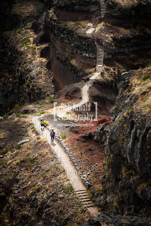 Walkers on a section of the path along the route of a Levada between Pico Areeiro and Pico Ruivo on the Portuguese Island of Madeira. Levada's were built on Madeira to help with water transportation from the wetter north-west of of the island to the drier south-east via irrigation channels.