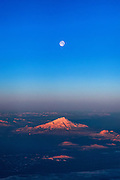 The full moon is in the sky over Mount Shasta, a 14,179-foot (4321 meter) volcano located in the Cascade Range in California. This is an aerial view captured over Lassen County, California.