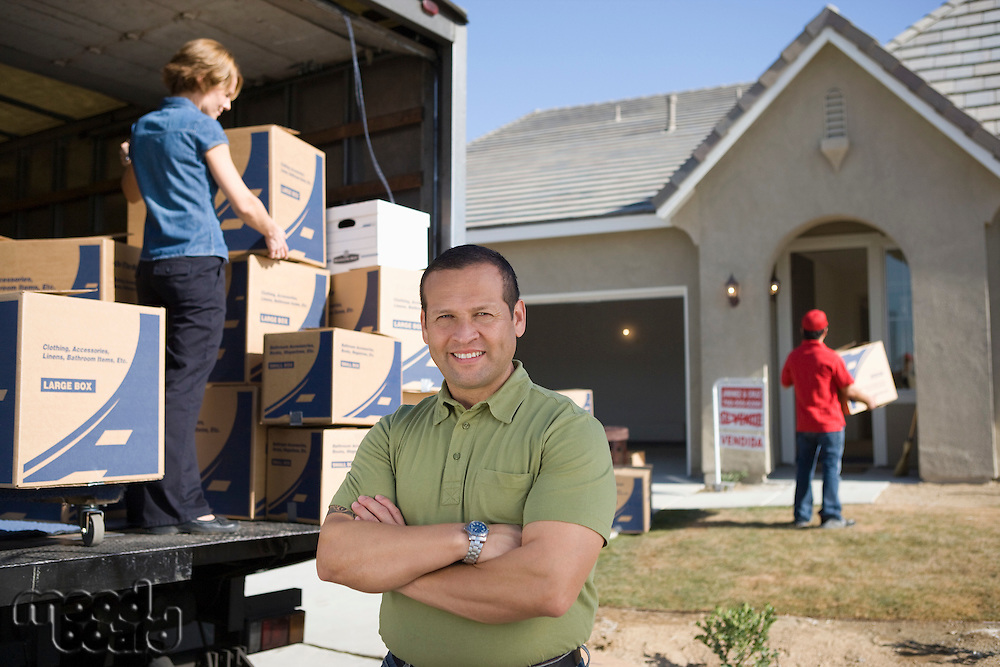 Portrait of man in front of truck with cardboard boxes