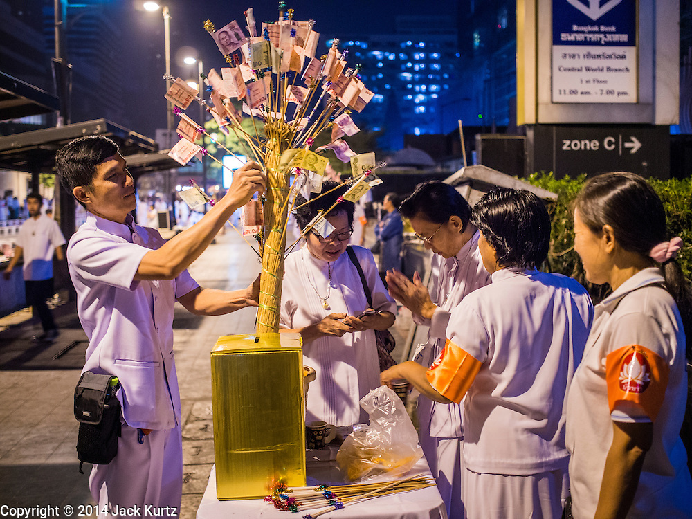 23 NOVEMBER 2014 - BANGKOK, THAILAND: People place monetary donations into a money tree at a mass alms giving ceremony in Bangkok Sunday. 10,000 Buddhist monks participated in the ceremony on Rajadamri Road in front of Central World shopping mall. The alms giving was to assist Buddhist temples in the insurgency wracked southern provinces of Thailand, where Buddhist monks on their alms rounds have been targeted by Muslim extremists. The ceremony was sponsored by Wat Phra Dhammakaya, the center of the Dhammakaya Movement, a Buddhist sect founded in the 1970s. The temple has become active in Thai politics.    PHOTO BY JACK KURTZ