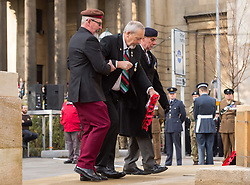 © Licensed to London News Pictures. 10/11/2019. Bristol, UK. Remembrance Day parade and wreath laying at the Cenotaph in Bristol city centre. Picture of a disabled veteran being helped laying wreaths. Photo credit: Simon Chapman/LNP.