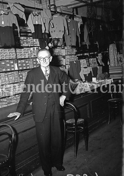 Portrait in front of counter in what appears to be a clothes shop. A lady stands behind the counter to the right of picture. Names, date and location unknown.<br /> (Part of the Independent Ireland Newspapers/NLI Collection)