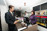Manager communicating with cashier at bar counter