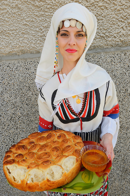 Young woman in Balkan dress offering bread and honey at the Celebration of the opening of a new Tahini-production factory in Kondovo village, Eastern Rhodope mountains, Bulgaria