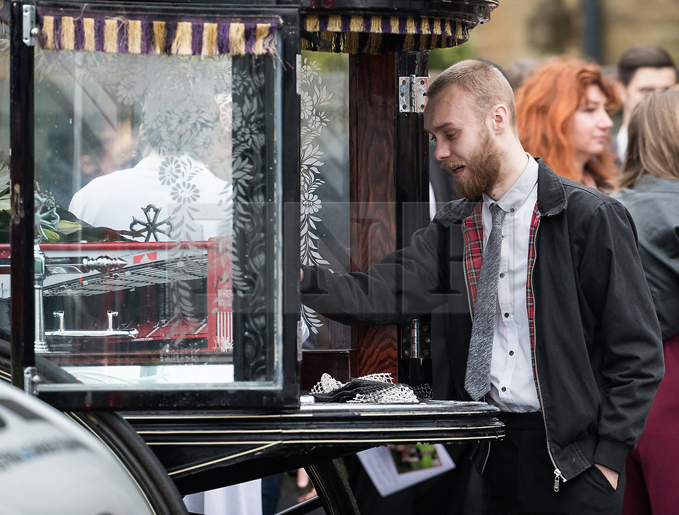© Licensed to London News Pictures . 20/12/2017. Manchester, UK. A mourner touches his hand to Sam's coffin in the hearse , outside the church after the service . The funeral of 14-year-old Sam Berkley at Christ Church in Denton , East Manchester . Mourners wear red and white , the colours of Hattersley FC , for whom Berkley played . Amongst their number are pupils and friends from Audenshaw School . Berkley died after being hit by a grey BMW near junction 3 of the M67 in Hyde , East Manchester , on 1st December 2017 . Photo credit: Joel Goodman/LNP