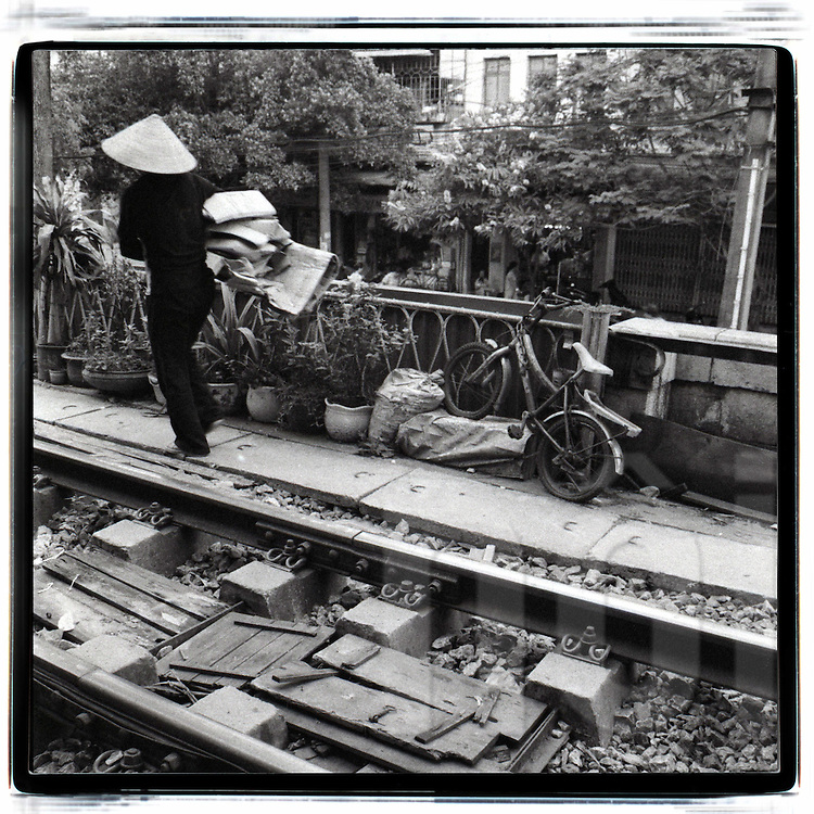 A vietnamese woman carries cardboards along the railway in Hanoi. She wears a conic hat a black clothes. A bicycle for kids is parked close from a bunch of green plants.