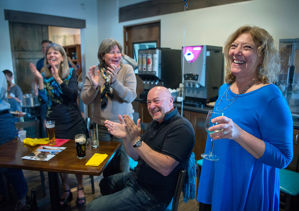 em050817b/a/Gail Ansheles, right, a kindergarten teacher at El Dorado Community School, is congratulated by her friends after seeing her win the Jeoparty game show during a watch party in Santa Fe, Monday May 8, 2017.  (Eddie Moore/Albuquerque Journal
