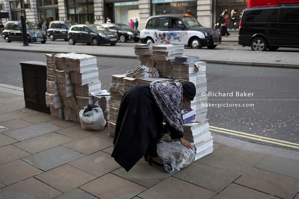 A woman stoops near bundles of Evening Standard newspapers in Piccadilly, on 9th November 2017, London, England.