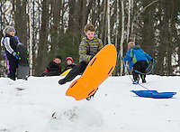 The Boys and Girls Club take in a day of sledding at Memorial Sledding Hill on Wednesday.  Isaiah gets good air off one of the jumps while children wait their turn.  (Karen Bobotas/for the Laconia Daily Sun)