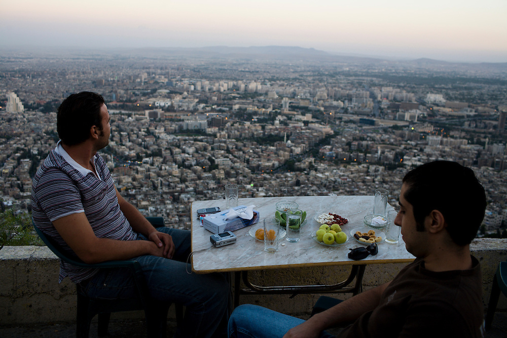 Syria, Damascus, general view of the city from a mountain, two young man in a coffee table.