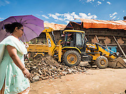 02 AUGUST 2015 - BHAKTAPUR, NEPAL:  A woman in Bhaktapur walks past a crew removing debris from the earthquake that hit Nepal in April 2015. Bhaktapur was badly damaged in the earthquake the hit Nepal in April 2015. The Nepal Earthquake on April 25, 2015, (also known as the Gorkha earthquake) killed more than 9,000 people and injured more than 23,000. It had a magnitude of 7.8. The epicenter was east of the district of Lamjung, and its hypocenter was at a depth of approximately 15 km (9.3 mi). It was the worst natural disaster to strike Nepal since the 1934 Nepal–Bihar earthquake. The earthquake triggered an avalanche on Mount Everest, killing at least 19. The earthquake also set off an avalanche in the Langtang valley, where 250 people were reported missing. Hundreds of thousands of people were made homeless with entire villages flattened across many districts of the country. Centuries-old buildings were destroyed at UNESCO World Heritage sites in the Kathmandu Valley, including some at the Kathmandu Durbar Square, the Patan Durbar Squar, the Bhaktapur Durbar Square, the Changu Narayan Temple and the Swayambhunath Stupa. Geophysicists and other experts had warned for decades that Nepal was vulnerable to a deadly earthquake, particularly because of its geology, urbanization, and architecture.      PHOTO BY JACK KURTZ