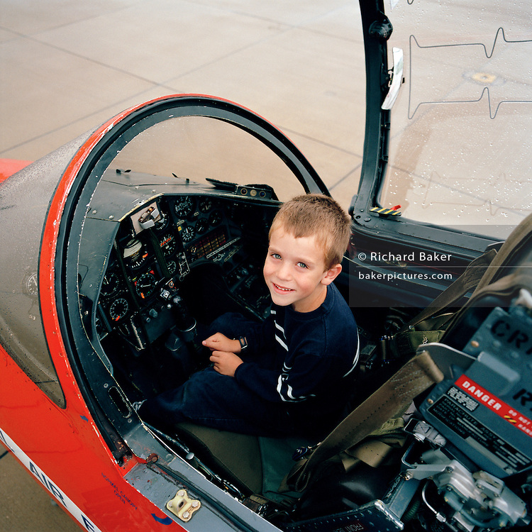 A young boy sits in BAE Systems Hawk cockpit of the 'Red Arrows', Britain's Royal Air Force aerobatic team.
