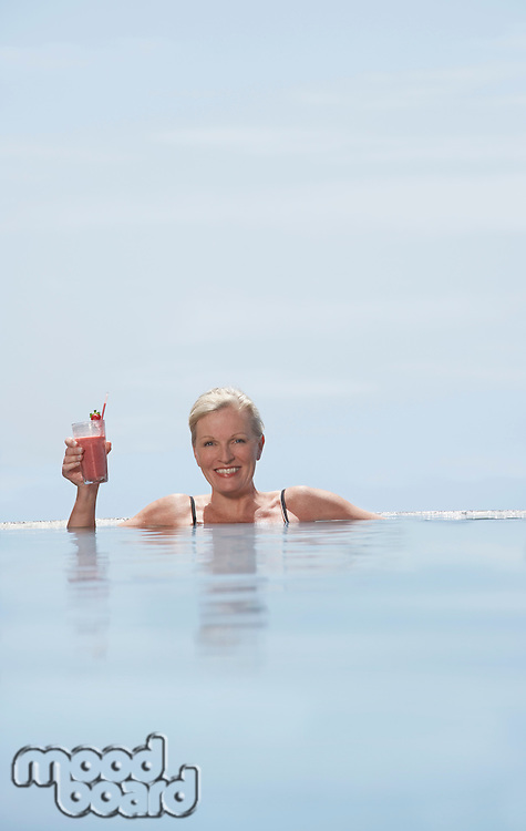 Mature woman holding daiquiri relaxing in pool