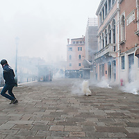 VENICE, ITALY - DECEMBER 14: A 'No Global' protester runs though several tear gas capsules during clashes at an anti-fascist rally on December 14, 2013 in Venice, Italy. There were clashes today between police and protesters as far-right and far-left groups demonstrated near Venice train station. (Photo by Marco Secchi/Getty Images)