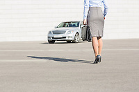 Low section of businesswoman carrying briefcase while walking towards car on street
