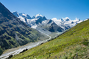 "The icy Bernina Range rises above Ova da Roseg river valley, near Pontresina, Switzerland, in the Bernina Alps, Europe. Tschierva Glacier flows from the peaks clustered on left: Piz Bernina (4049 m), Piz Scerscen (3971 m) and Piz Roseg (3937 m). At right (west), Roseg Glacier flows from Piz Glüschaint (3594 m). Val Roseg is in the Swiss canton of Graubünden (or Grisons / Grigioni / Grischun); the lower Roseg Valley is in Pontresina, whereas the upper valley is in an exclave of Samedan Municipality. Hike from Pontresina up Roseg Valley to Fuorcla Surlej for stunning views of Piz Bernina and Piz Roseg, finishing at Corvatsch Mittelstation Murtel cable car. Walking 14 km, we went up 1100 meters and down 150 m. Optionally shorten the hike to an easy 4 km via round trip lift. The Swiss valley of Engadine translates as the ""garden of the En (or Inn) River"" (Engadin in German, Engiadina in Romansh, Engadina in Italian), and is part of the Danube basin."