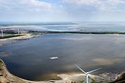 Nederland, Zuid-Holland, Rotterdam, 18-02-2015; De Slufter, grootschalige opslagplaats voor vervuild havenslib. De verontreinigde baggerspecie komt voort uit het onderhoudsbaggerwerk in de Rotterdamse haven waarbij de haven op diepte wordt gehouden. De vierkante plaat is een drijvend eiland voor broedende visdieven.<br /> The Slufter area in the South-West of the Netherlands, large-scale depot of contaminated harbor sludge from the Port of Rotterdam. Along the edge of the Slufter windmills are built. The square plate is a floating island for nesting common terns.<br /> luchtfoto (toeslag op standard tarieven);<br /> aerial photo (additional fee required);<br /> copyright foto/photo Siebe Swart