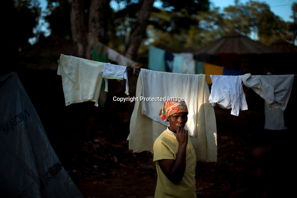 A woman makes her way along a row of tents at a Red Cross-run camp in the Mathare section of Nairobi, May 25, 2008. More than 300,000 Kenyans were left homeless after President Mwai Kibaki's disputed re-election in December triggered ethnic clashes, killings and looting. Some aid workers estimate that half of them have returned home, but many are still too afraid or don't have enough resources to do so despite reassurances from the power-sharing government.