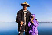 Portrait of a man from belonging to Mishmi tribe of Arunachal Pradesh wearing a cane hat, poses with his daughter while crossing the river at Sadia.