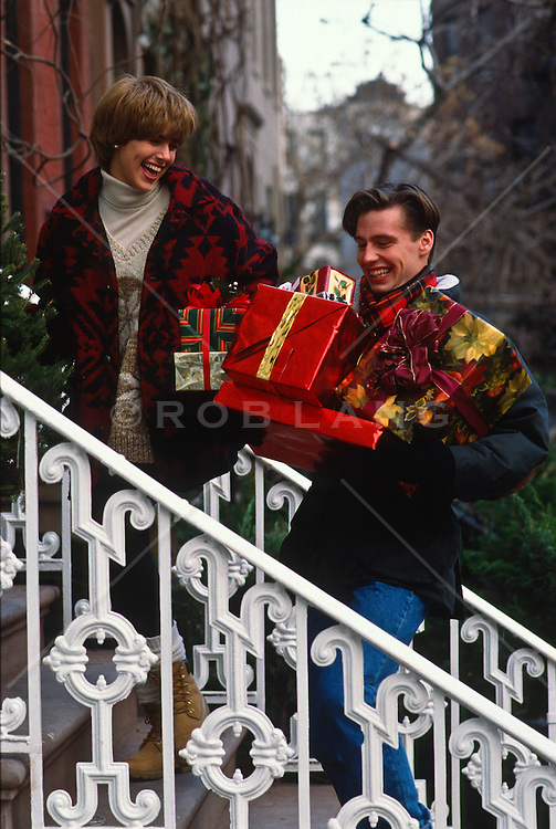 Couple Walking up stairs of a brownstone building while carrying Christmas presents