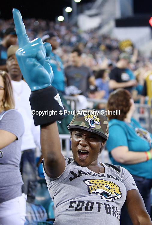 A Jacksonville Jaguars holds up a foam finger as she cheers during the 2015 week 11 regular season NFL football game against the Tennessee Titans on Thursday, Nov. 19, 2015 in Jacksonville, Fla. The Jaguars won the game 19-13. (©Paul Anthony Spinelli)