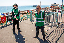 © Licensed to London News Pictures. 30/05/2020. Brighton, UK. Brighton and Hove council officers manage the entry of people on to the beach as the Coronavirus lock down rules apply. Thousands of members of the public take to the seaside on the hottest day of the year so far.  Photo credit: Hugo Michiels/LNP