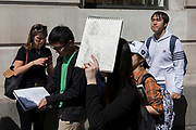Carrying recent sketches of the Gherkin and the Lloyds of London Building, foreign students of Architecture and the work of Sir Norman Foster, walk through the City of London, the capital's ancient, financial district, on 14th May, in London, England. (Photo by Richard Baker / In Pictures via Getty Images)